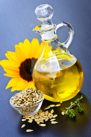 Sunflower oil bottle stock photo, Sunflower oil bottle with raw seeds and flower by Elena Elisseeva