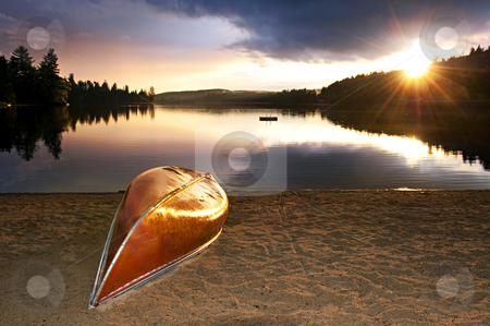 Lake sunset with canoe on beach stock photo, Sun setting over tranquil lake with canoe on beach by Elena Elisseeva