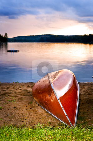 Lake sunset with canoe on beach stock photo, Canoe on beach at sunset on lake shore by Elena Elisseeva