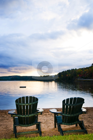 Wooden chairs at sunset on beach stock photo, Two wooden chairs on beach of relaxing lake at sunset by Elena Elisseeva