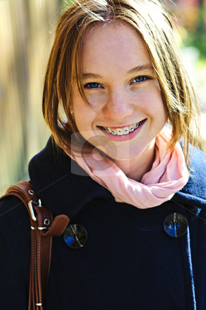 Happy teenage girl in coat stock photo, Portrait of teenage girl smiling wearing coat and scarf by Elena Elisseeva