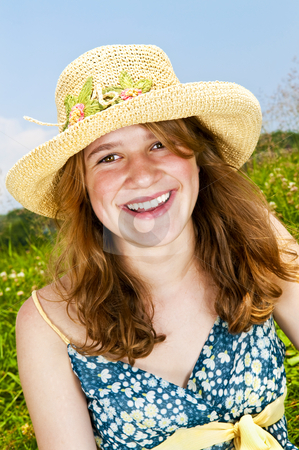 Portrait of young girl smiling in meadow stock photo, Portrait of young teenage girl smiling on summer meadow in straw hat by Elena Elisseeva