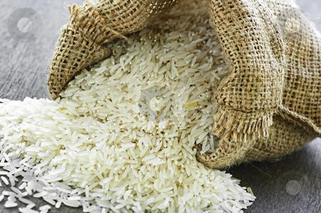 Long grain rice in burlap sack stock photo, Raw long grain white rice grains in burlap bag by Elena Elisseeva