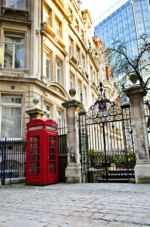 Telephone box in London stock photo, Red telephone box near old and new buildings in London by Elena Elisseeva