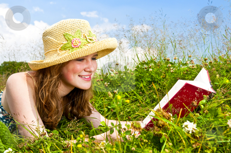 Young girl reading book in meadow stock photo, Portrait of teenage girl reading book in summer meadow with straw hat by Elena Elisseeva