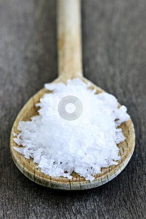 Sea salt stock photo, Sea salt on wooden spoon over wooden table background by Elena Elisseeva