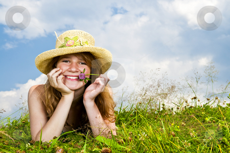 Young girl laying in meadow stock photo, Young teenage girl laying in summer meadow resting chin on hand holding flower by Elena Elisseeva