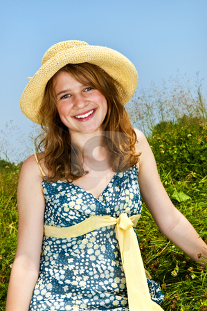 Young girl sitting in meadow stock photo, Young teenage girl sitting on summer meadow in straw hat by Elena Elisseeva