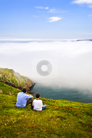 Father and son at ocean coast stock photo, Father and son looking at foggy ocean view in Newfoundland by Elena Elisseeva