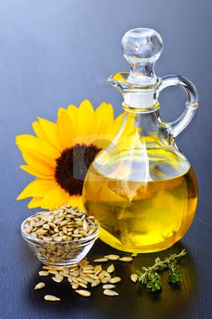 Sunflower oil bottle stock photo, Sunflower oil bottle with raw seeds and flower by Elena Elisseeva