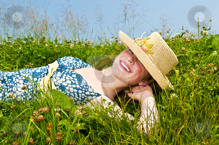 Young girl laying on meadow stock photo, Young teenage girl laying on summer meadow amid wildflowers in straw hat by Elena Elisseeva