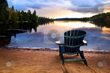 Wooden chair at sunset on beach stock photo, Wooden chair on beach of relaxing lake at sunset by Elena Elisseeva
