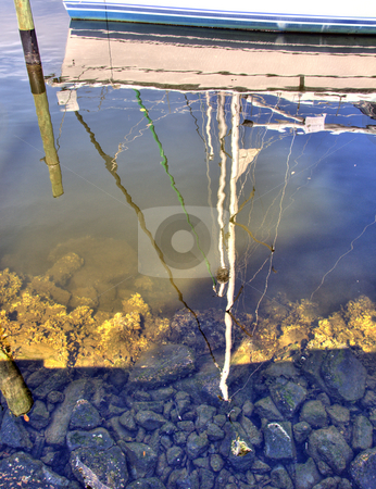 Reflections of sail boat stock photo, Reflections of a sail boat moored close to shore. by Steve Carroll