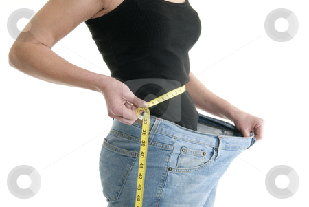Successful diet stock photo, A Caucasian woman measures her waist while wearing pants that are too large. by Christy Thompson