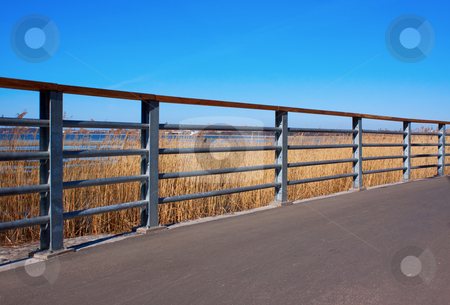 Perspective view of metal handrail stock photo, Perspective view of metal handrail, clear blue sky and walkway by Igor Sandra