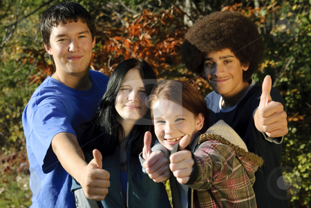 Ethnic teen thumbs up stock photo, Teens of various ethnic backgrounds outdoors giving a thumbs up. Focus on teen girl second from right. by Christy Thompson