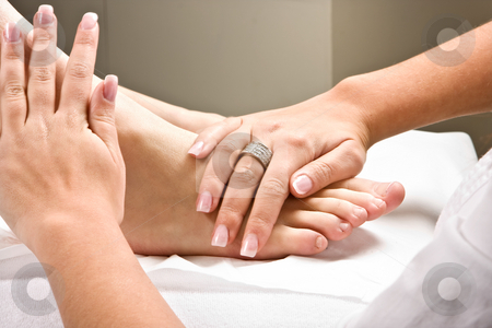Massaging feet stock photo, Woman's hands giving a healthy foot massage by Anneke
