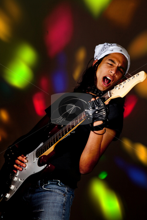 In the lights stock photo, Young handsome rock singer against a dark background with spot lights by Anneke