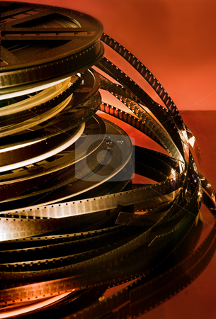 Old movie rolls  stock photo, Stacked rolls of old movies against a red background by Anneke