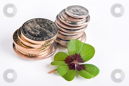 Lucky dollars stock photo, Four-leaf clover on a stack of dollar coins by Anneke