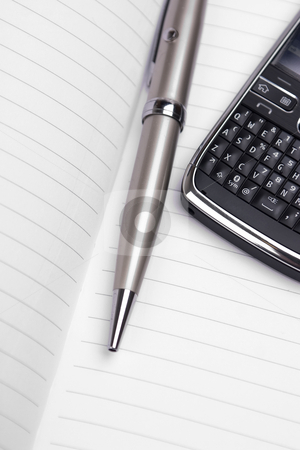 Pen and cellphone stock photo, Pen and cellphone on top of a notebook. by ??ystein Litleskare