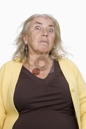 Portrait of a Senior Female stock photo, Portrait of a senior woman in a yellow sweater. She is looking at the camera with an ominous expression. Vertical shot. Isolated on white. by Paul Burns
