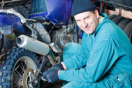 Mechanic in garage stock photo, Mechanic changing car tire in garage by Ruta Balciunaite