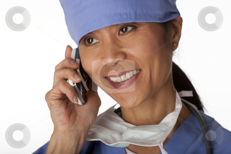 Medical Professional in Scrubs on the Phone. Isolated stock photo, Closeup, cropped view of an Asian female medical professional wearing scrubs and talking on a cell phone. Horizontal shot. Isolated on white. by Edward Bock