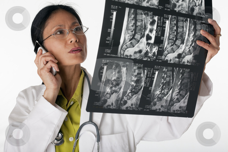 Doctor Reading MRI scan stock photo, Asian female doctor looking at an MRI scan while talking on a cellphone. Horizontal shot. Isolated on white. by Edward Bock