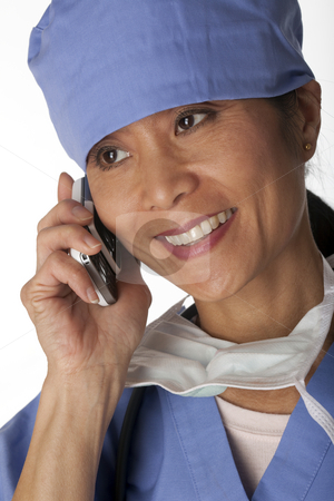 Medical Professional in Scrubs on the Phone stock photo, Closeup, cropped view of an Asian female medical professional wearing scrubs and talking on a cell phone. Vertical shot. Isolated on white. by Edward Bock