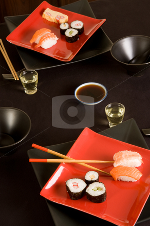 Sake and sushi stock photo, Japanese dinner setting with sushi, chopsticks and sake by Anneke