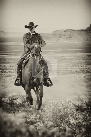 Cowboy on Horseback stock photo, A man wearing old western attire rides a horse across a country plain. Vertical shot. by Troy Boman
