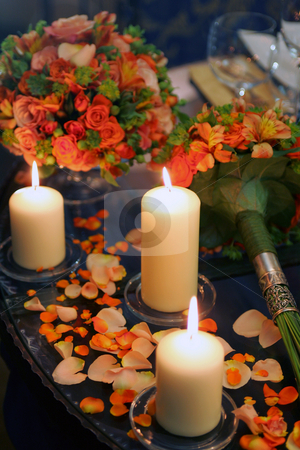 Burning candles flowers and petals stock photo, Burning candles on table scattered with flower petals from bouquet of flowers. by Martin Crowdy