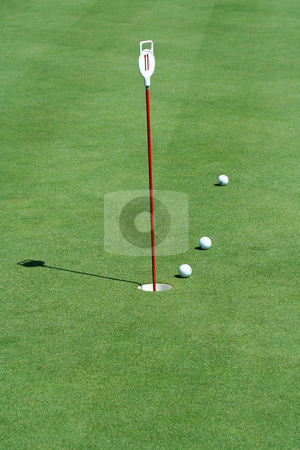 Practice putting green with golf balls stock photo, A Practice putting green with golf balls by Jim Mills