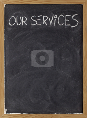 Our services blackboard sign stock photo, Our services - white chalk handwriting on blackboard with eraser smudges, copy space below by Marek Uliasz
