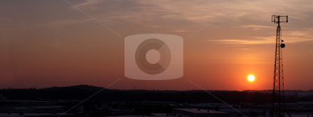 Panoramic Orange Cell Tower Silhouette stock photo, The silhouette of a cell phone tower shot against the orange cast of the setting sun. by Chris Hill