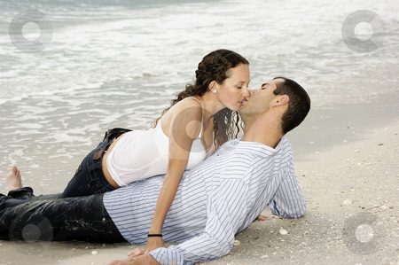 Wet young adult couple kissing at the beach stock photo, A young american couple are on the beach kissing, the woman is on top of the man by Stephen Orsillo