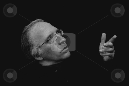 Looking pointing stock photo, Man looking up gesturing with hand in this three quarter view portrait with dark background by Stephen Orsillo