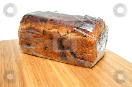 Raisin Cinnamon Bread Loaf stock photo, Wrapped Loaf of sliced cinnamon raisin bread on a wooden cutting board by Lynn Bendickson