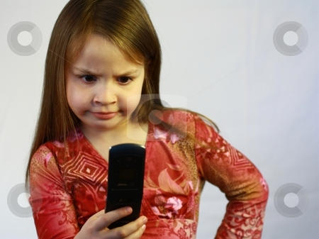 Cute little girl with cell phone in hand. stock photo, Little girl with cell phone by Gregory Dean