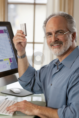 Businessman Sitting at Computer With Credit Card stock photo, A businessman sitting in front of a computer monitor and holding up a credit card.  He is smiling at the camera. Vertical shot. by Edward Bock