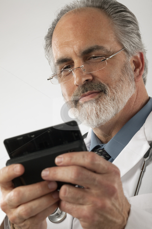 Doctor Texting on a Cell Phone stock photo, Close-up of a doctor wearing glasses and a lab coat and texting on a cell phone. Vertical shot. by Edward Bock