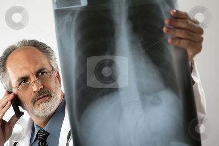 Doctor Looking at X-Ray and Using Cell Phone stock photo, Selective focus image of a doctor wearing glasses and a white lab coat and looking intently at an x-ray while using his cell phone. Horizontal shot. by Edward Bock