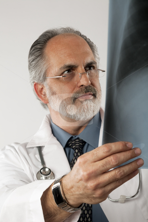 Doctor Looking at X-ray. Isolated stock photo, Portrait of a doctor wearing eyeglasses and a white lab coat and looking intently at an x-ray. Vertical shot. Isolated on white. by Edward Bock