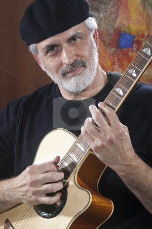Middle-Aged Man With Acoustic Guitar stock photo, Portrait of a middle-aged man wearing a black beret and t-shirt and playing an acoustic guitar. He is looking at the camera. Vertical shot. by Edward Bock