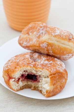 Jam donut with bite taken out stock photo, Jam donut with bite taken out and a cup in the background by Robert Anthony