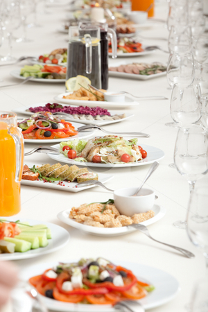 Served restaurant table stock photo, Long served restaurant table with snacks and salads by Ruta Balciunaite