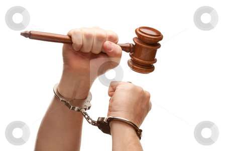 Handcuffed Man Holding Wooden Gavel on White stock photo, Handcuffed Man Holding Wooden Gavel in His Fist Isolated on a White Background. by Andy Dean