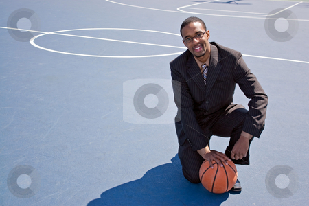 Basketball Professional stock photo, A young African American man in a business suit posing on the basketball court with a ball.  Works great for coaching or recruitment concepts. by Todd Arena
