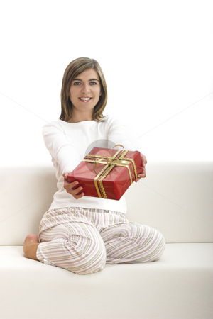 Happy woman with gifts stock photo, Woman in pajama seated on a sofa holding a Christmas gift by ikostudio